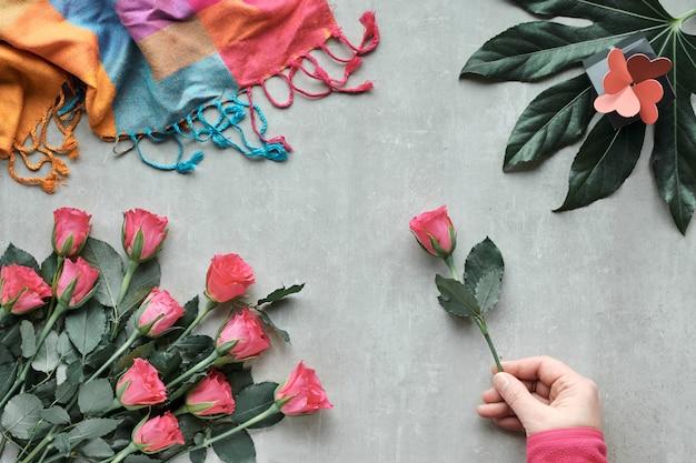 フラット横たわっていた、バラの花、ピンクのスカーフ、ギフトボックスとエキゾチックな葉のコンポジション。単一のバラの花を持っている手。明るい石の平面図。バレンタイン、誕生日または母の日の概念。