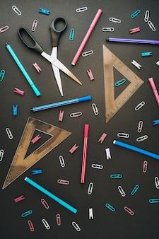 Плоская композиция с линейкой ножниц и школьными принадлежностями на темноте