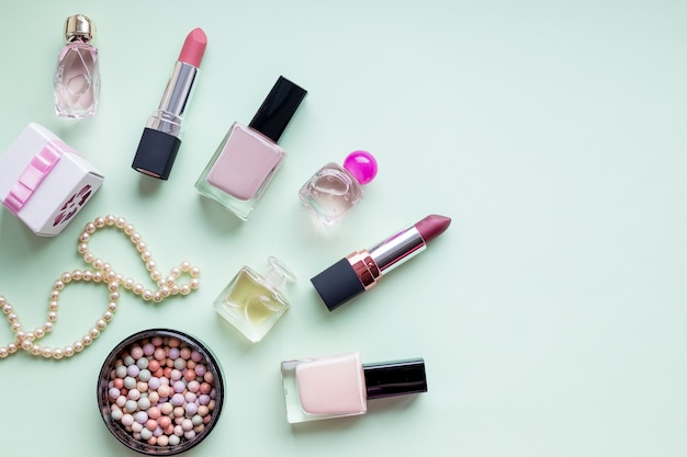 Flat lay composition with skin foundation, powder and beauty accessories. decorative composition with lipstick and blush top view on soft green background.