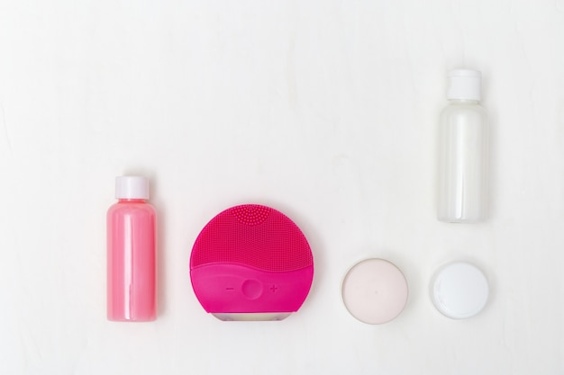 Flat lay composition with skincare products, face brush, cleanser in bottles, moisturizer.