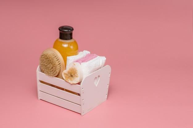 분홍색 배경에 스파 화장품과 수건으로 평면 위치 구성