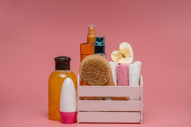 Плоская композиция со спа-косметикой и полотенцем на розовом фоне