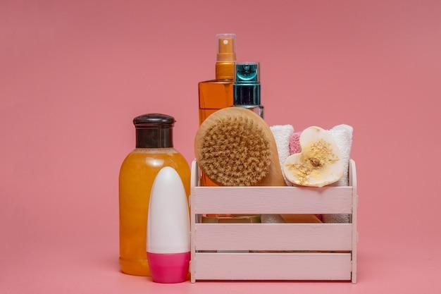 Плоская композиция со спа-косметикой и полотенцем на розовом.
