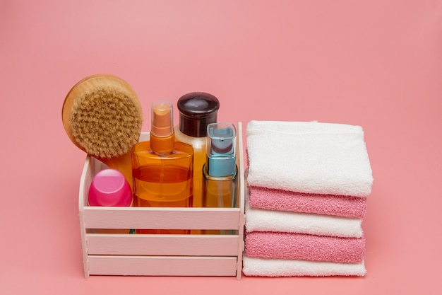 Flat lay composition with spa cosmetics and towel on pink background.