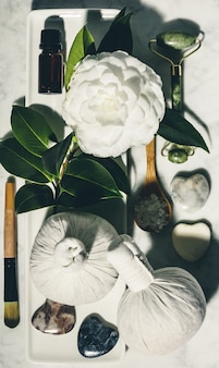 Flat lay composition with spring camelia flower and various beauty care products on white marble table