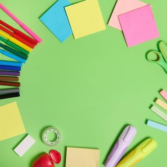 Плоская композиция с канцелярскими принадлежностями или школьными принадлежностями, разбросанными по кругу на светло-зеленом фоне с копией пространства. снова в школу концепции.