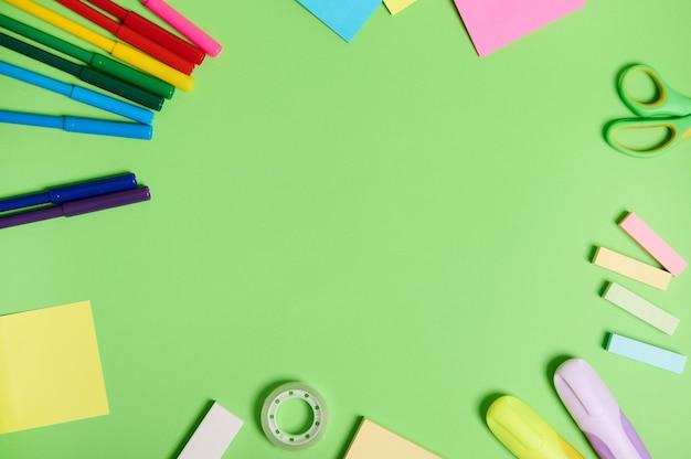 Плоская композиция с канцелярскими принадлежностями или школьными принадлежностями, разбросанными по кругу на светло-зеленом фоне с копией пространства. концепция дня учителя