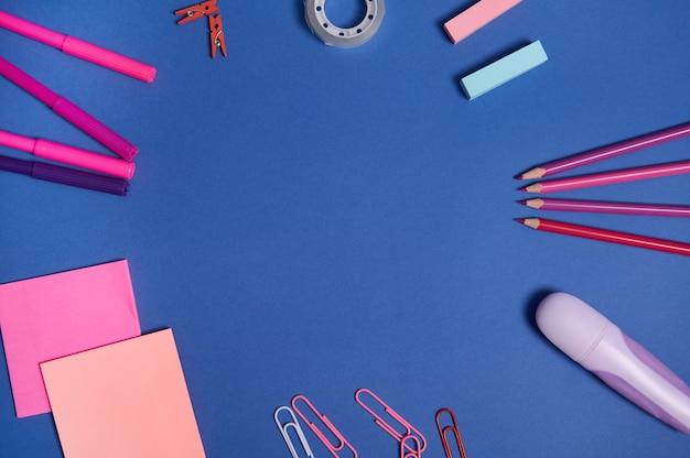 Плоская композиция с канцелярскими или школьными принадлежностями в розовых фиолетовых тонах, разбросанными по кругу на синем фоне с копией пространства. концепция дня учителя