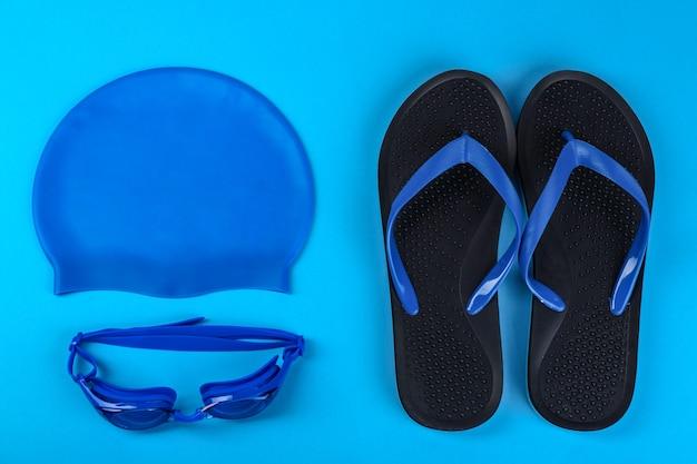 水色の背景に水泳アクセサリーとフラットレイ構成