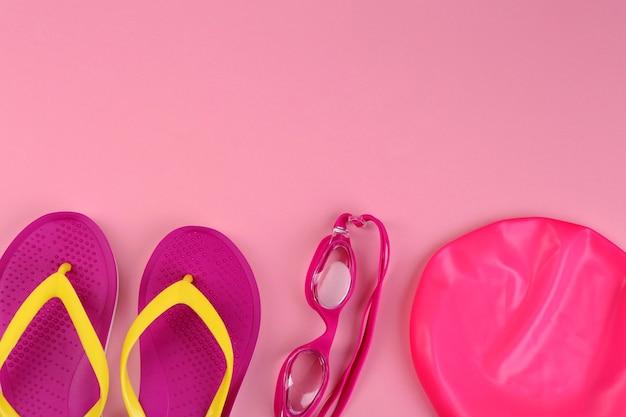 ピンクの背景に水泳アクセサリーとフラットレイ構成。テキスト用のスペース