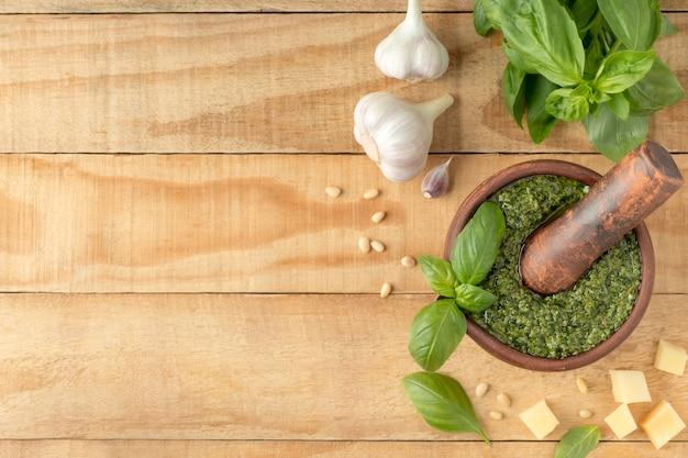 Плоская композиция с вкусным соусом песто в ступке и ингредиентами на деревянном столе