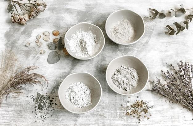 Композиция flat lay с приготовлением маски для лица из глины, натуральных ингредиентов в косметологии.
