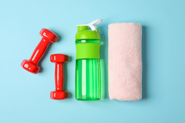 Flat lay composition with towel, dumbbells and fitness bottle on blue background