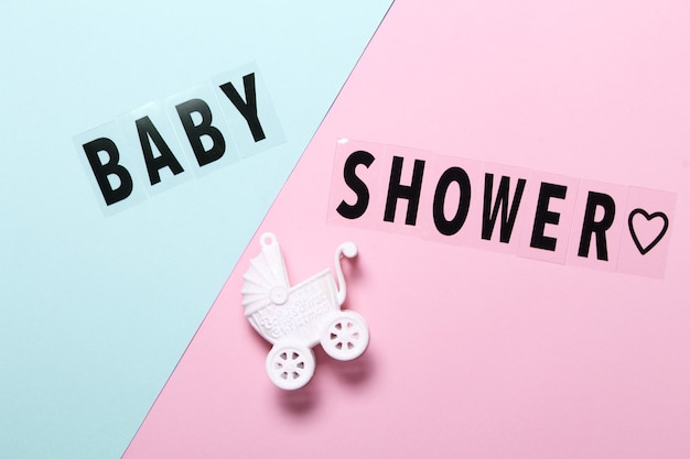 Flat lay composition with toy stroller and words baby shower on light blue and pink background background.