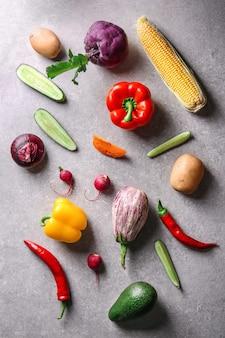 灰色の表面にさまざまな野菜を使ったフラットレイ構成