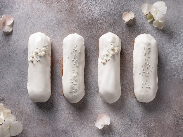 Flat lay composition with white chocolate glaze eclairs and hydrangea flowers. pastry filled with cream.