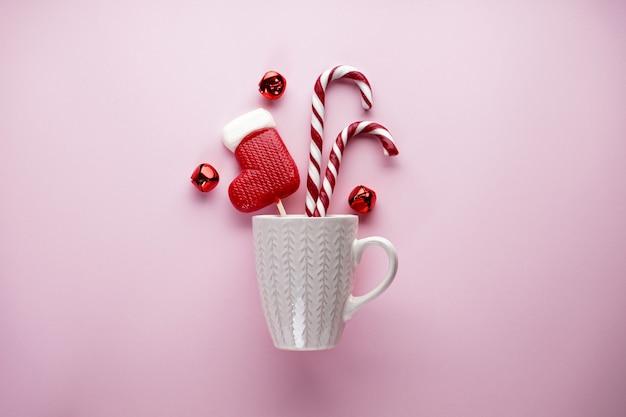 Плоская композиция с белой чашкой и рождественскими конфетами на розовом. новогодняя композиция.