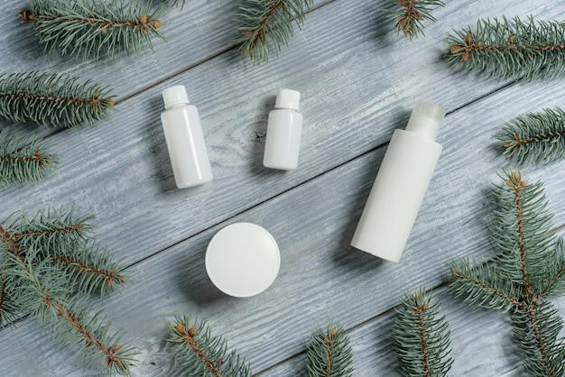 가벼운 나무 테이블에 화장품 및 전나무 가지 흰색 튜브와 평면 위치 구성.