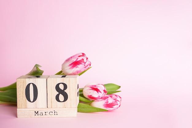 3月8日、木製のカレンダーとチューリップを使用したフラットレイ構成