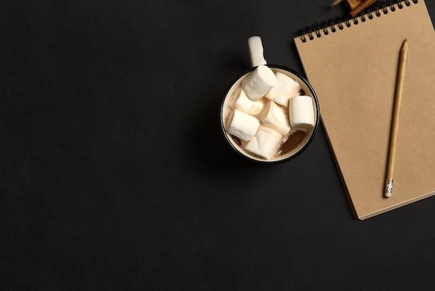 空の空白のシートと黒い背景、コピースペースにおいしい甘い白いマシュマロとホットココアドリンクのカップとクラフトメモ帳に木製の鉛筆でフラットレイ構成。クリスマスのコンセプト