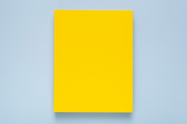 Flat lay composition with yellow notebook on blue background