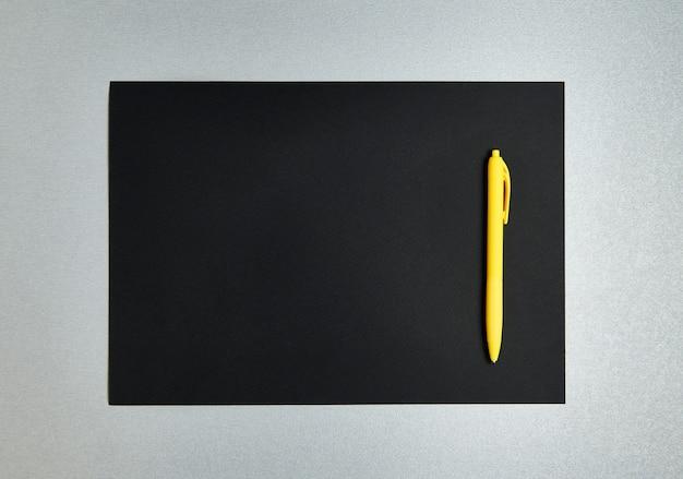 Плоская композиция с желтой ручкой на черной дизайнерской бумаге на сером фоне. вид сверху