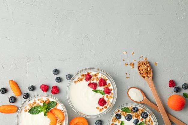 Плоская композиция с йогуртовыми десертами и фруктами на сером цементном фоне