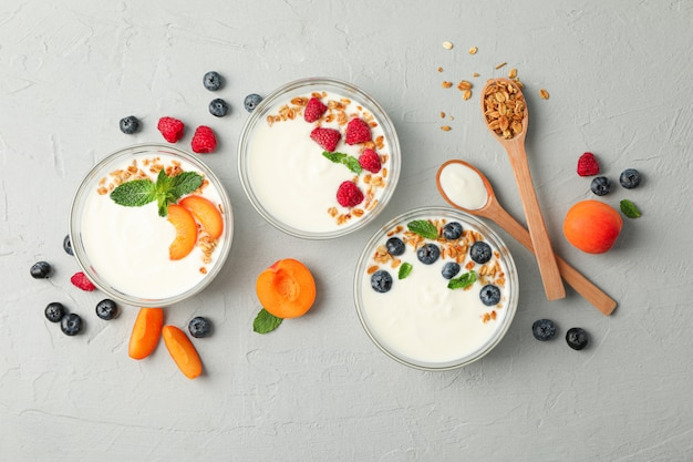 Flat lay composition with yogurt desserts and fruits on grey cement background