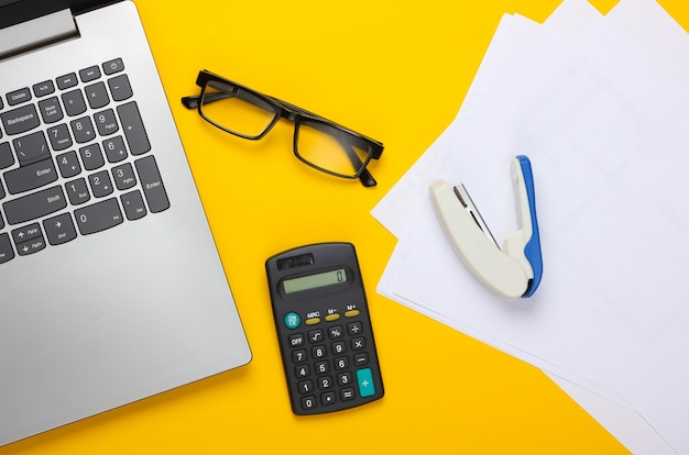Flat lay composition on a yellow. office workspace with laptop, calculator, glasses, stapler and paper