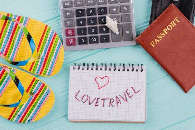 Плоская композиция концепции путешествия с паспортом, сандалиями и калькулятором на синем фоне. люблю путешествия, написанные на блокноте.