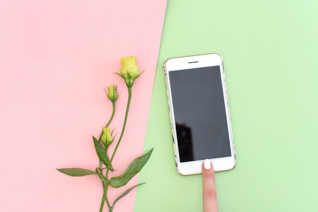 Flat lay concept of feminine finger with cell phone, silk and branch of artificial cotton flower.