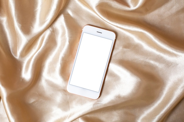 Flat lay concept of feminine light background with mobile phone on beige silk .