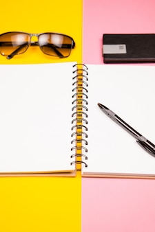 Плоская планировка писателя с бумажным блокнотом, ручкой, солнцезащитными очками и держателем для визиток на двухцветном фоне