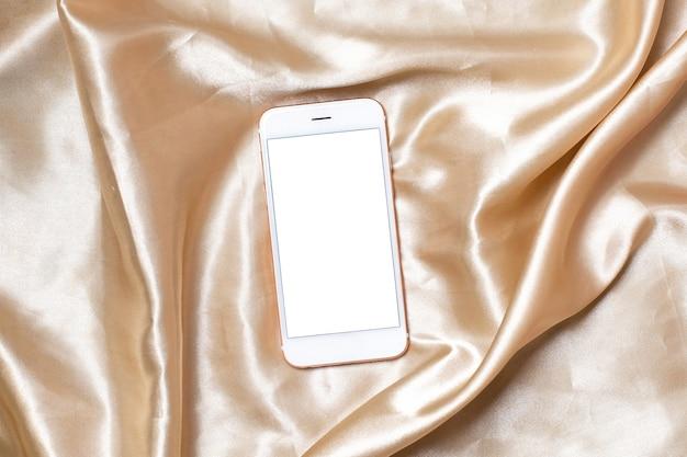 ベージュのシルクに携帯電話でフェミニンな明るい背景のフラットレイコンセプト。