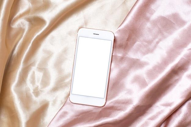 ベージュとピンクのシルクに携帯電話を使ったフェミニンな光のフラットレイコンセプト