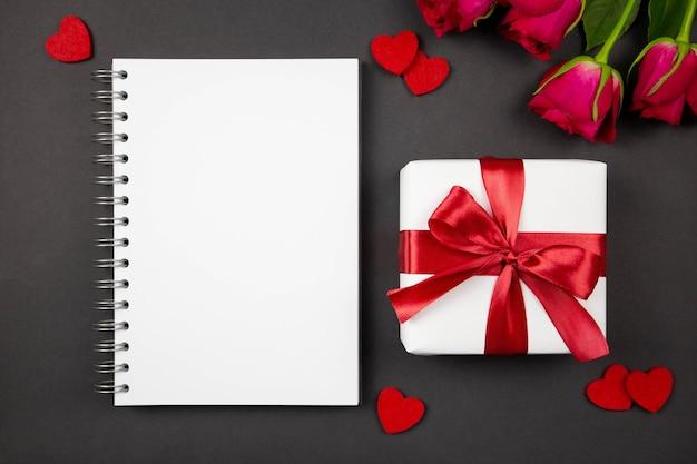 バレンタイン、記念日、母の日、誕生日のフラットレイコンセプト。紙のスパイラルノートと赤いリボン、ハート、バラのダークのギフトボックスが付いています。