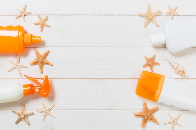 Flat lay concept summer travel vacation. sunscreen bottles with starfish on white wooden table with copy space.