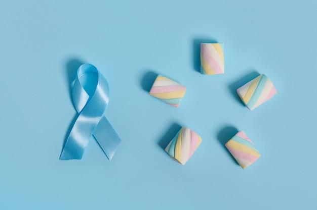 青いサテンのアウェアネスリボンと甘いマシュマロがコピースペースのある背景に五芒星の形で配置されたフラットレイの概念的な構成。 11月14日世界糖尿病デーのコンセプト