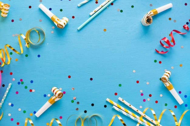 Flat lay of confetti and party whistles