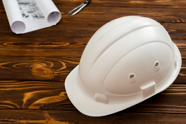 Flat-lay construction helmet with plans in background