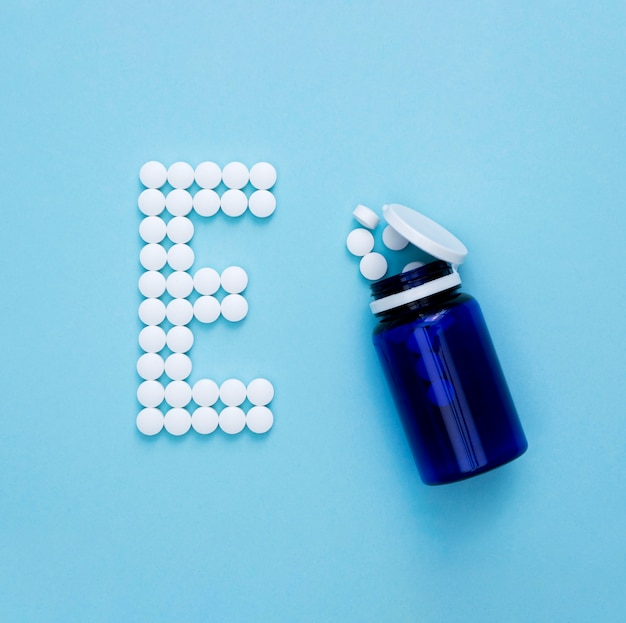 Flat lay of container with pills spelling letter e