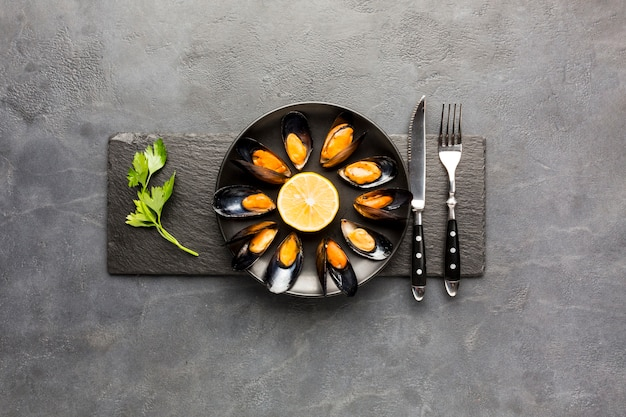 Flat-lay cooked mussels plate on slate