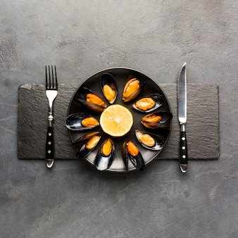 Flat-lay cooked mussels on slate with copyspace