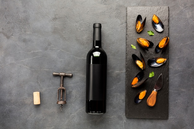 Flat-lay cooked mussels on slate with wine bottle