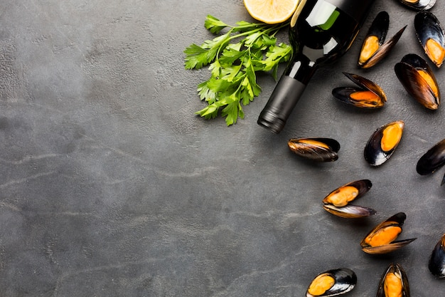 Flat-lay cooked mussels and wine bottle with copyspace