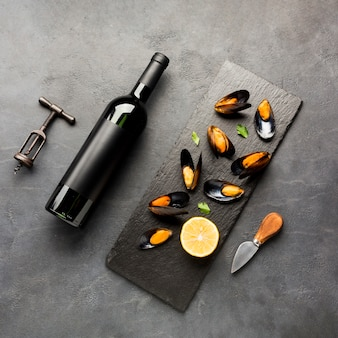 Flat-lay cooked mussels and wine bottle