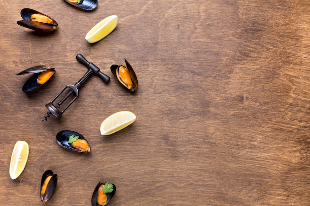 Flat-lay cooked mussels and wine opener with copyspace