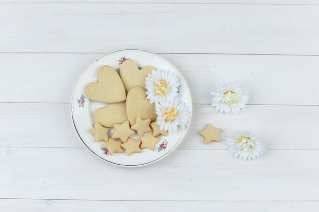 Biscotti piatti laici nella piastra con fiori su fondo in legno. orizzontale