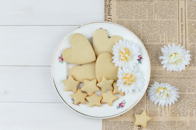 Flat lay cookies in plate with flowers on wooden and newspaper background. horizontal