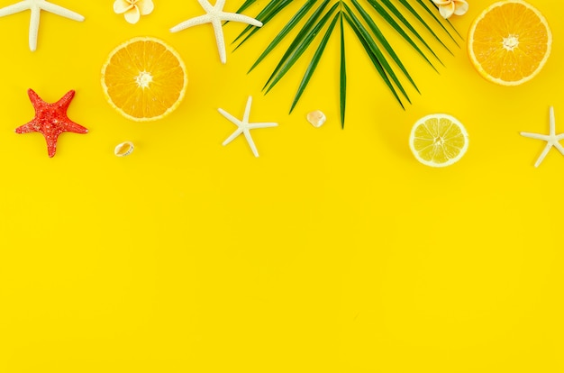Flat lay corner frame on yellow background. palm, starfish and orange